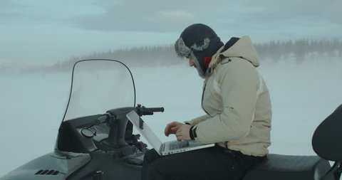 Young programmer who using notebook on snowmobile in adverse winter conditions. He is blowing into his hands to warm up. Yamal 2016 Red Epic 4k