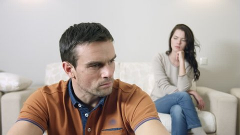 Sad couple sitting at home, disappointed husband folding his hands near the face and woman bowed her head sitting on the sofa