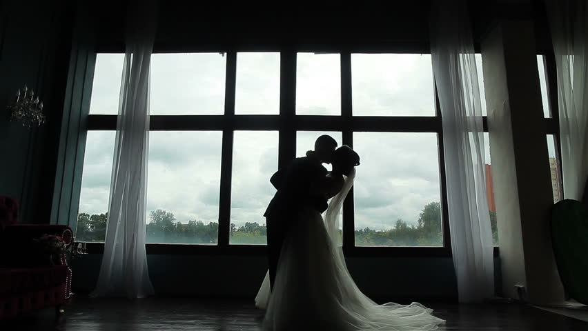 Confident groom meets happy bride first time seeing her in wedding dress silhouetted near window. Marrying couple embrace and kiss standing near huge window in room