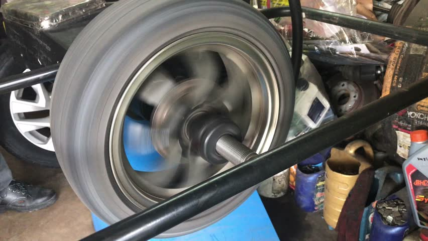 Man adjust balance of car wheel on special machine, closeup view | Shutterstock HD Video #22715251