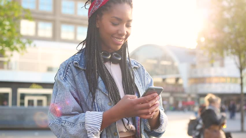 Black young woman typing on smart phone in Berlin. Smiling girl wearing a jeans jacket with lurred people and tram in Alexanderplatz on background.