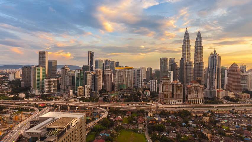 Beautiful and Dramatic Kuala Lumpur city skyline overlooking AKLEH expressway with busy light trails and national landmark from day to night. Kuala Lumpur, Malaysia. 4K UHD. Pan Camera Motion.