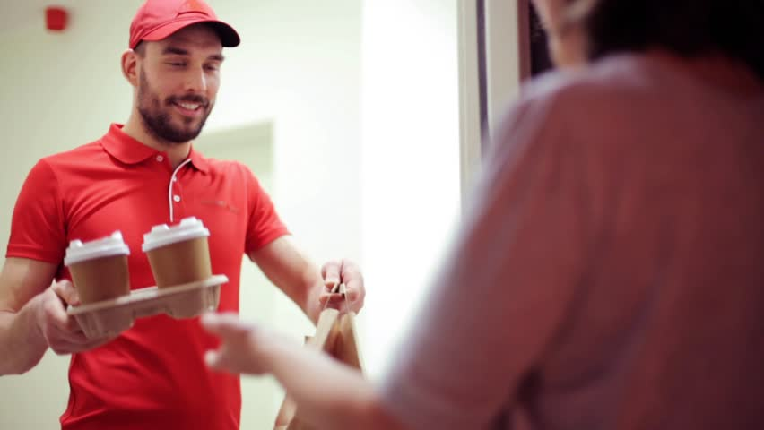 delivery, mail and people concept - happy man delivering coffee and food in disposable paper bag to customer home and taking payment
