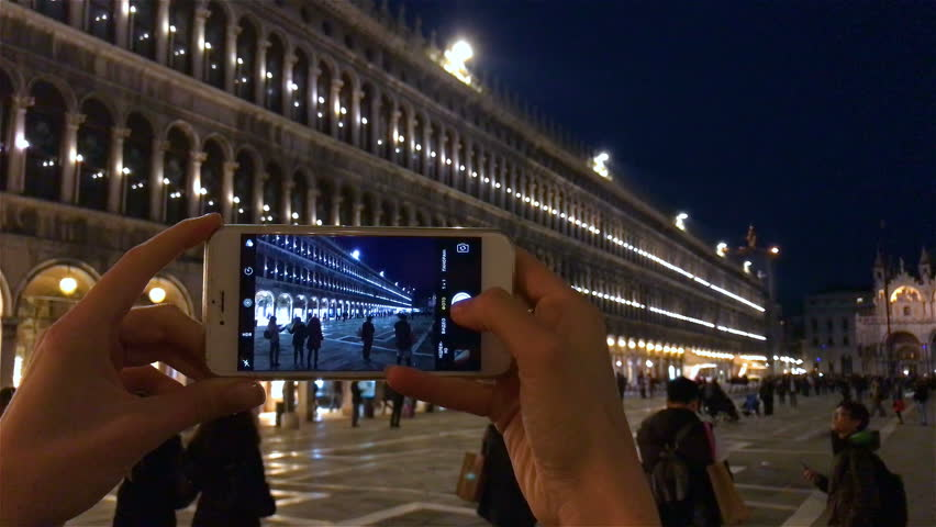 VENICE ITALY 25 NOV 2016: phone photo at night by smartphone mobile camera. Young woman hands taking picture background, shooting video, holding smart cell device. Night lights at San Marco, Venezia .