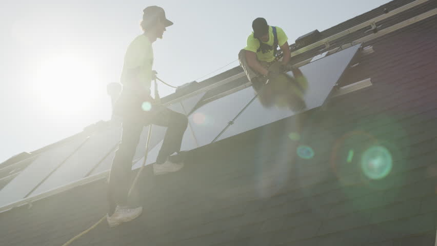 Medium panning low angle shot of workers installing solar panel on roof / Mapleton, Utah, United States | Shutterstock HD Video #22769671