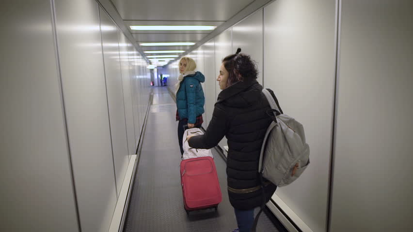 Airport. Two young women running on your flight. Blonde girl with a suitcase in a hurry to pass through the pipe to the plane. Brunette with a backpack on his shoulders in a great mood.