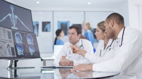 4K Medical research team in a meeting, looking patient scans via video link Dec 2016-UK