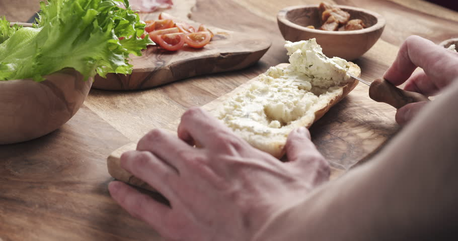 man spread cream cheese with herbs over baguette in slow motion, 4k 60fps prores footage