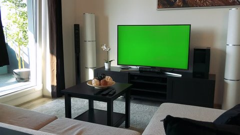 A TV with a green screen in a cozy living room