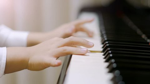 Child playing piano. Side view of a child playing piano. Close up on piano keys, child hands and fingers.