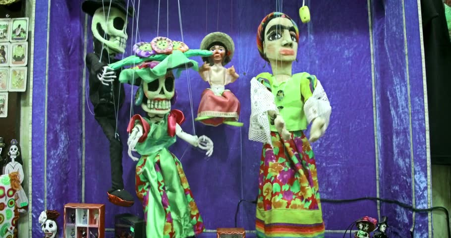 SAN DIEGO, USA - NOVEMBER 2016; Colorful mexican dancing puppets. Traditional folk art marionettes in national costumes. Day of the Dead celebration symbols.
