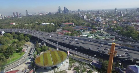 A fast flyover of Mexico City features a highway with traffic as well as the children's museum as well as the downtown skyline.