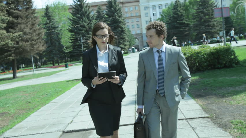 Female consultant and her client walking through the park discussing business options