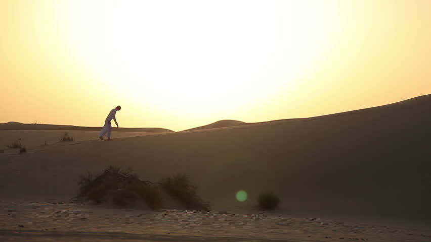 Weary man goes in the desert at sunset