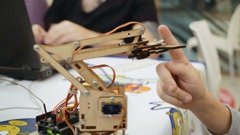 Small toy robot arm helps children to learn and understand robotics technology. Robots and automation are substitute for future human labor.