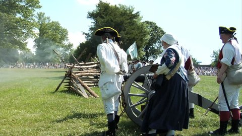 NEW JERSEY - JUNE 2015 - Reenactment, large-scale, epic American Revolutionary War anniversary recreation -- Continental Army Artillery Cannon in battle with Molly Pitcher helping with gun, cannonball