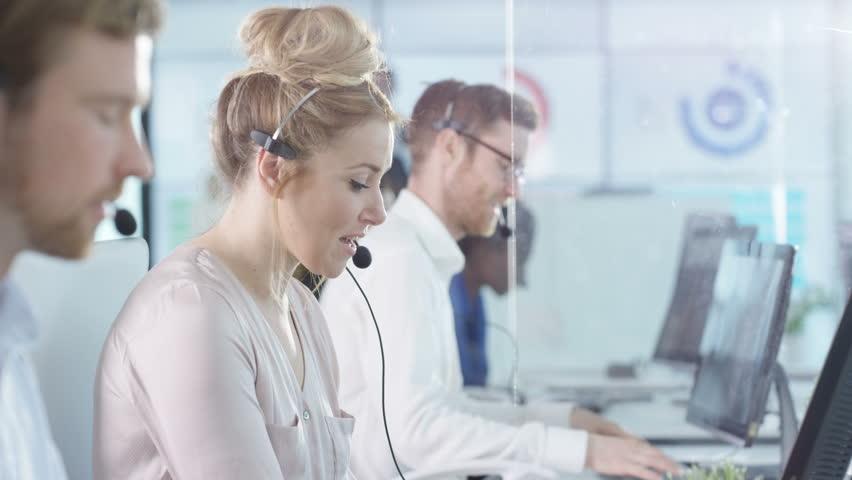 4K Portrait smiling customer service operator taking calls in busy call center Dec 2016-UK | Shutterstock HD Video #22933891