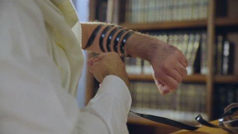 Jewish man put on  the hand a tefillin