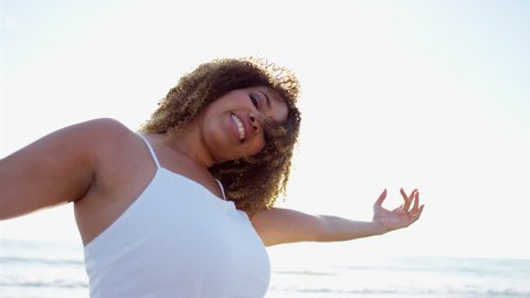 Portrait of smiling plus size Ethnic African American female in a white dress having fun on vacation by the ocean RED DRAGON