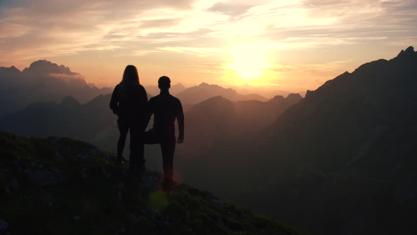 Aerial, edited - Raising above hiking couple watching and admiring beautiful sunset in the mountains | Shutterstock HD Video #22960801