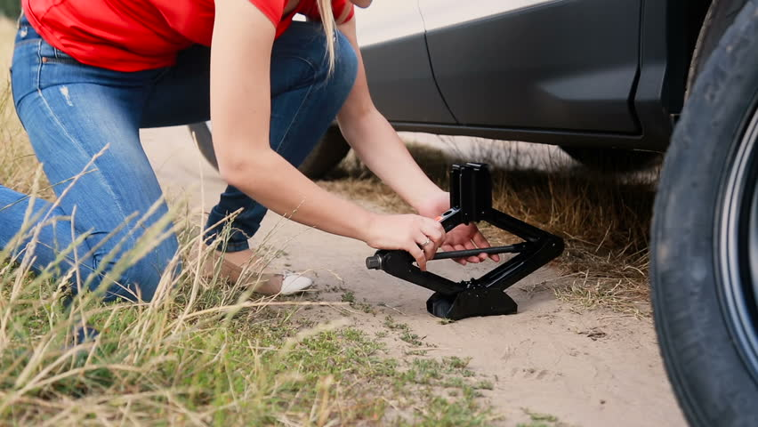 Young woman using jack-screw to lift a car before changing flat tire on dirt road at countryside