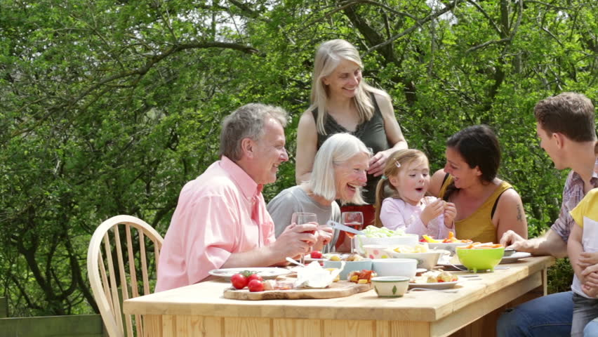 Family Are Sitting Outdoors In Summer To Have A Picnic Meal
