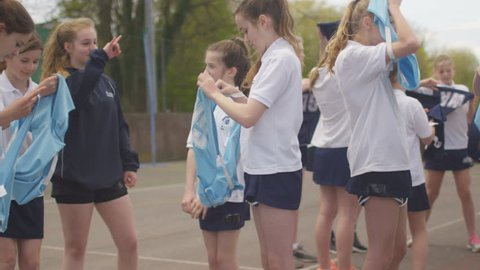 4K 2 Young netball teams on outdoor court putting on bibs at beginning of a game Dec 2016-UK