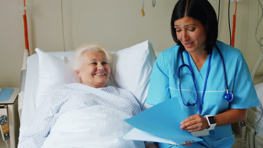 Female doctor discussing report with senior patient in hospital 4k | Shutterstock HD Video #22984621
