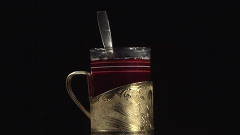 black tea in the cup holder of gold in a dark room