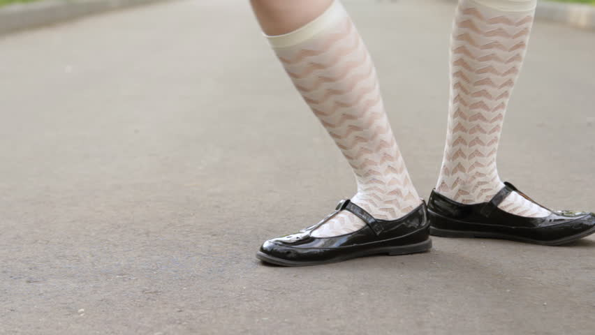 Seamless looped dancer's legs close-up. Girl dancing solo jazz swing dance on the city's square pavement. Funny dance.