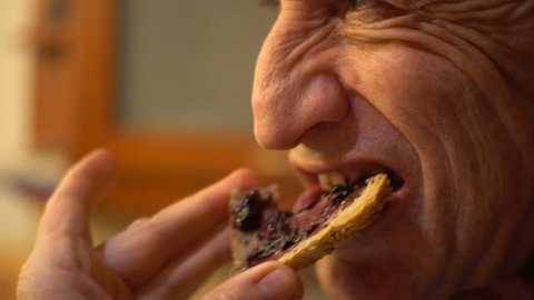 Man biting breakfast toast with blueberry jelly