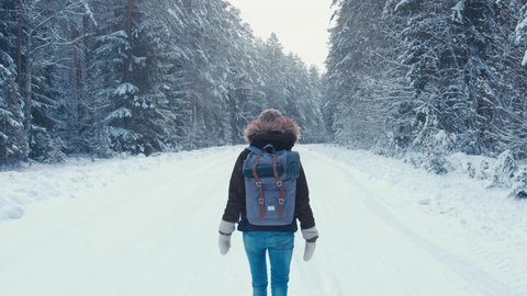 RL PAN Young female hiking with a backpack in beautiful winter forest, walking on a road away from the camera, light snowfall. 4K UHD, 60 FPS SLO MO, RAW edited footage
