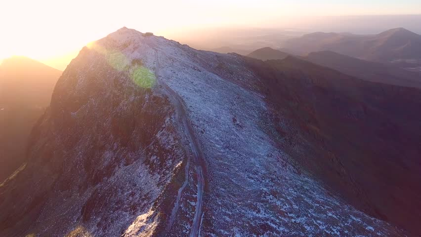 Aerial shot following the Snowdonia mountain railway to the summit of Snowdon at sunrise.