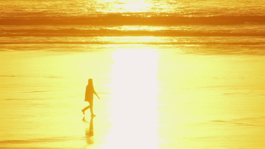 Woman walking during sunset at beach, dissolves into the sunlight reflection and continues on her walk.