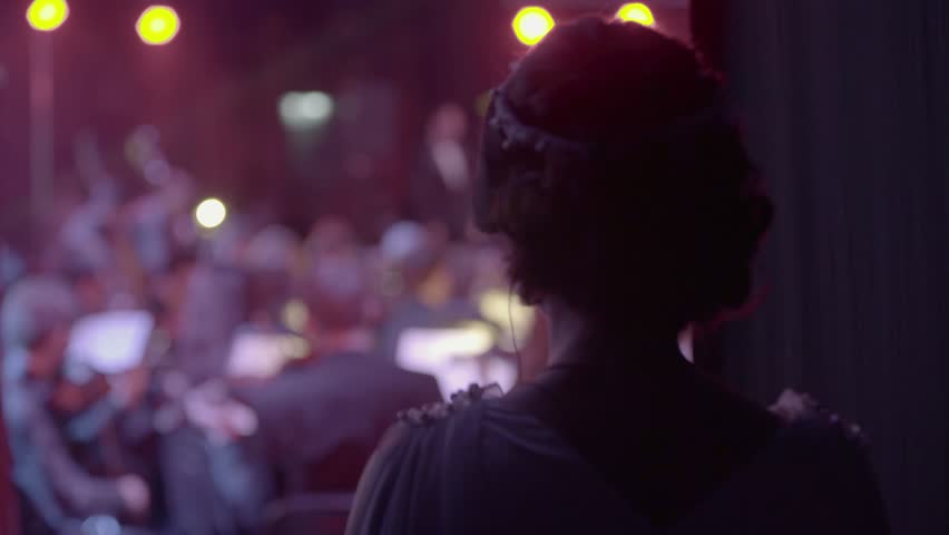 The singer looks at the orchestra from behind the scenes before going on stage | Shutterstock HD Video #23044951