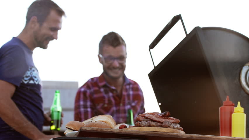 Two happy male friends making barbecue with fried buns sausages and meat drinking beer outdoors in slowmotion