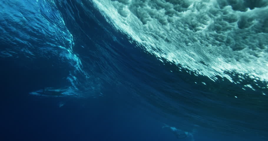 Under water view of blue ocean wave from behind. Barreling wave with sunlight and bubbles