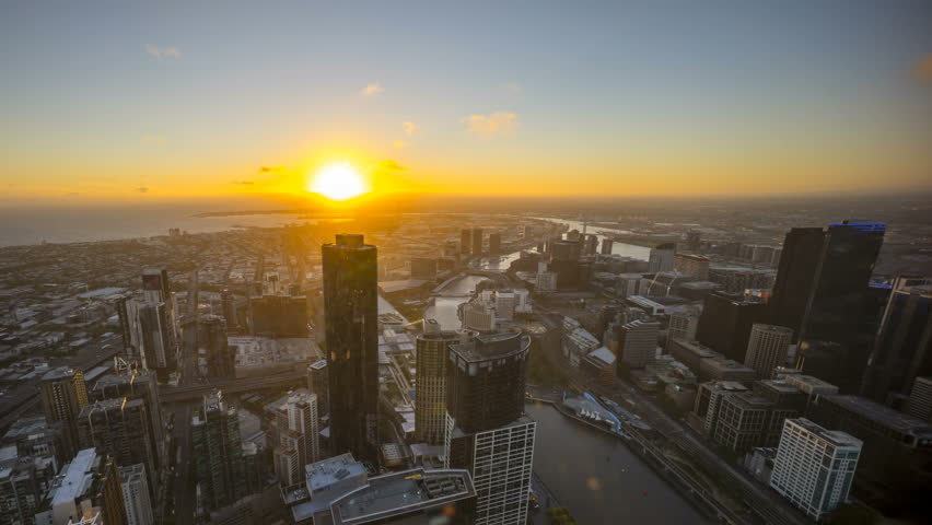 An aerial view of Melbourne cityscape including Yarra River and Victoria Harbour in the distance. Timelapse during sunset with beautiful sun ray bursting through fast moving clouds. Timelapse pan left | Shutterstock HD Video #23062651