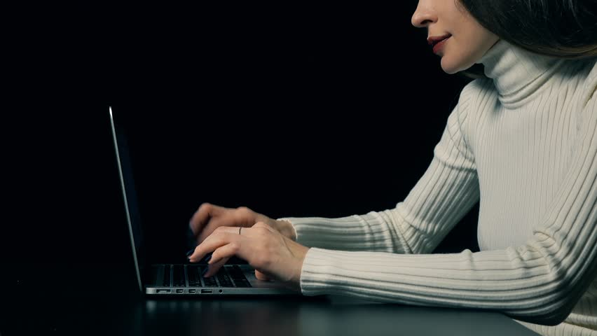 Attractive brunette woman typing on her portable computer against dark background. 4K video | Shutterstock HD Video #23109271