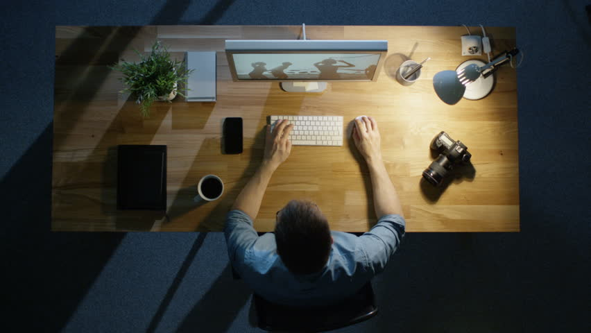 Top View of a Young Photographer Processing Photographs on His Desktop Computer Late at Night. Table Lamp Illuminates His Desk. Camera, External Hard Drive and Notebook Lie Beside Him.   Shutterstock HD Video #23128030