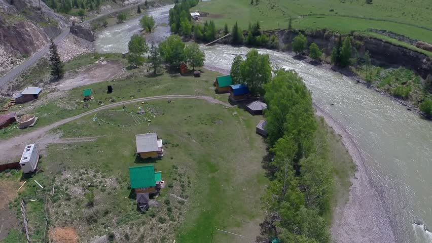 Mountain village. time lapse shot. The top view on the river in Altai. The settlement at the small river. Green meadows at the river. Camera GoPro. The camera slowly removes the top view