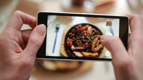 Trendy man in a restaurant make photo of food with mobile phone camera