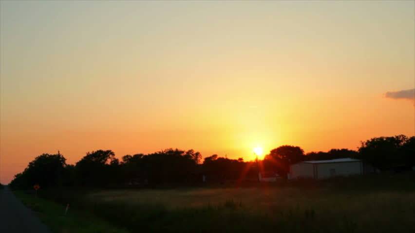A lazy Texas sun just before sunset appears to follow travelers along a rural stretch of highway.