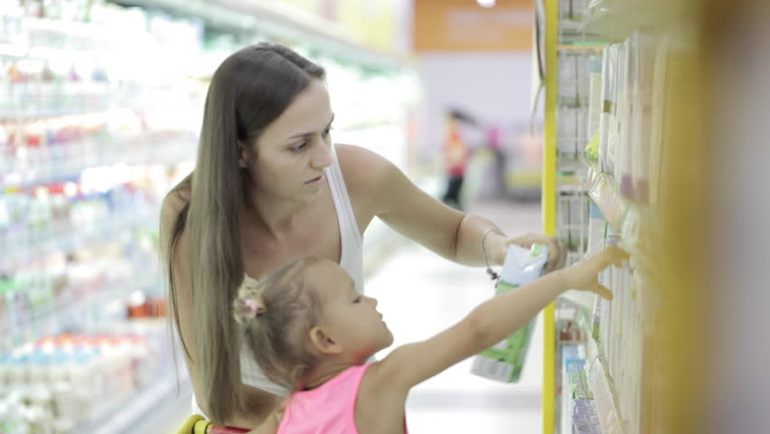Young attractive woman with cute daughter in shopping cart choosing a milk in grocery section at supermarket and baby drops a milk | Shutterstock HD Video #23156344