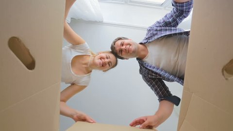 POV of happy young couple opening big cardboard box