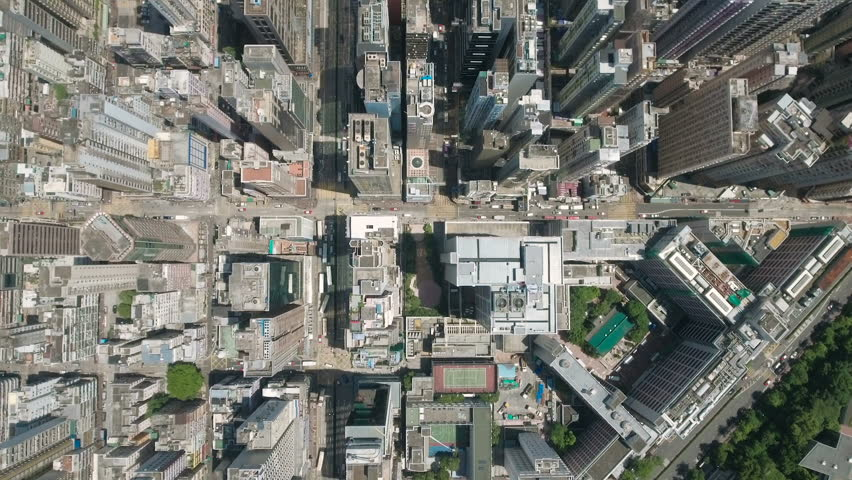 Abstract aerial drone footage of rooftops and streets in the densely populated Kowloon area in Hong Kong, one of Asia's most iconic modern cities.