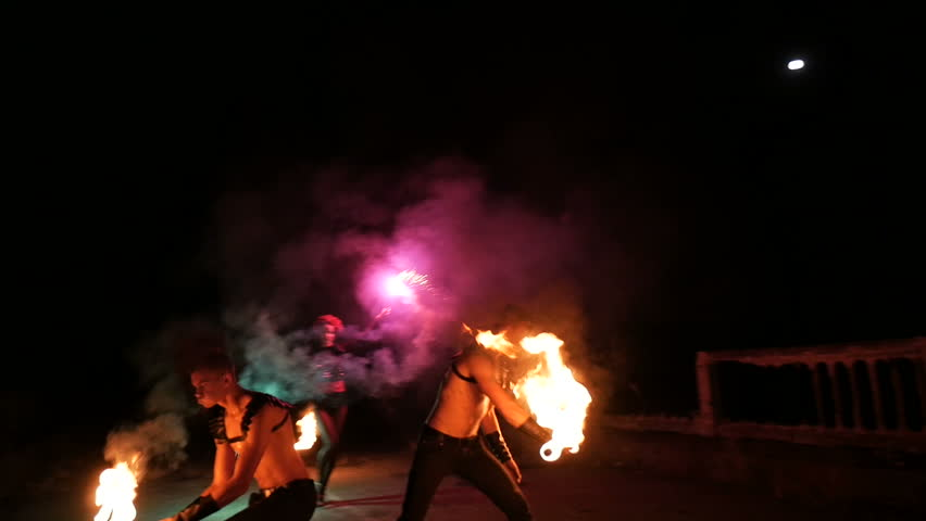 two boys artist performing fire show at night. fire breather spitting flame in slow motion