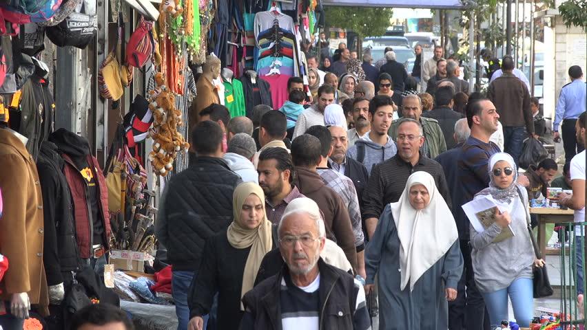 AMMAN, JORDAN - NOVEMBER 2016: Crowds of pedestrians walk through a popular shopping street in downtown Amman, Jordan