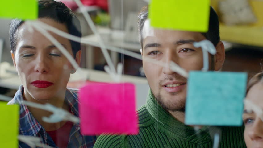 Close up of creative startup workers looking at glass wall planner with post-it notes discussing ideas and drawing arrows