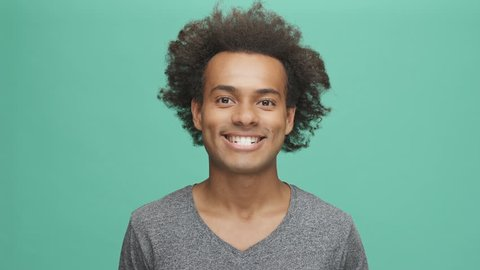 Young afro american man with humorous funny face expressions isolated on a green background